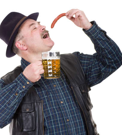 Elderly man holding a beer belly and sausage on white background photo