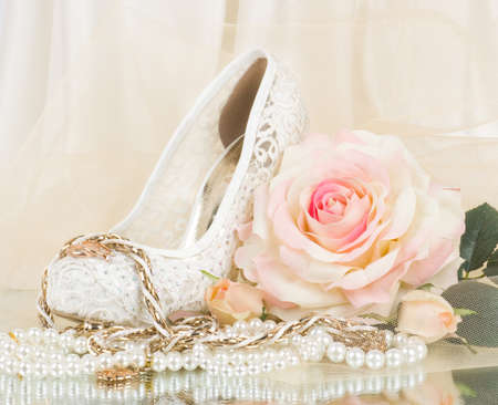 The beautiful bridal rose with wedding shoe and beads 스톡 콘텐츠