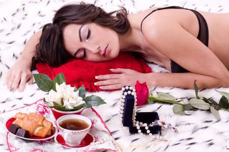 Beautiful young brunette woman in bed with gifts on a Valentine s day Stock Photo - 12962138