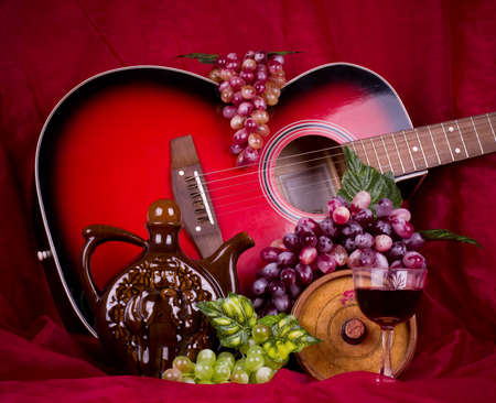 composition with wine, grape and guitar on red photo
