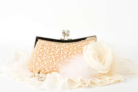 Fashionable handbag and pearl jewelry on white background  photo