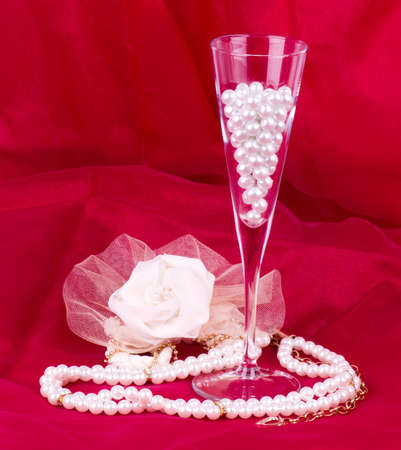 White flower, pearls and beads on red background Banque d'images