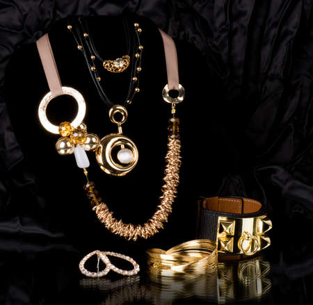 Golden jewelry on black background photo