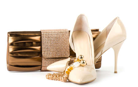 Sexy fashionable shoes with handbag and golden jewelry on white background