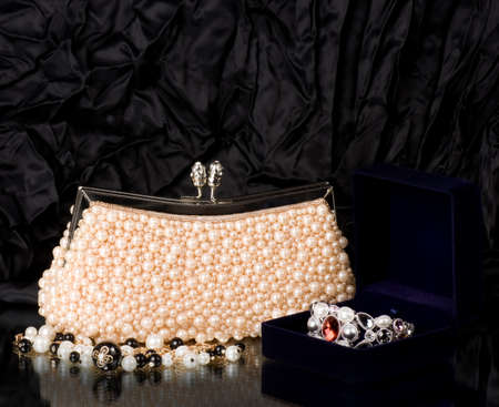 Sexy fashionable handbag with pearl jewelry on black background Stock Photo - 12885977