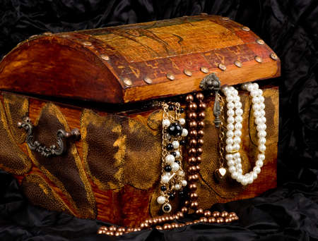 treasure box: Vintage wooden treasure trunk with jewelry on black background