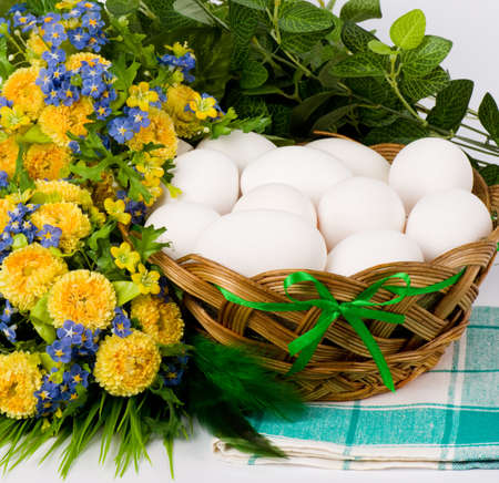 Basket with Easter eggs and springflowers on white background photo