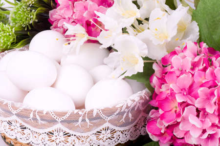 Basket with Easter eggs and spring flowers photo