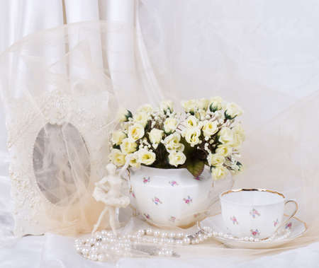 Beautiful spring flowers in a glass teapot on background photo