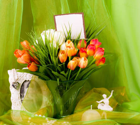 Beautiful spring flowers in a glass vase and ballet-dancer on green photo