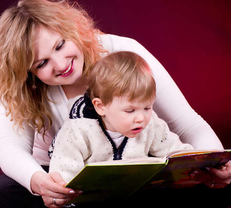 twelve month old: Mother and baby boy reading book and smiling  on red background Stock Photo