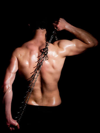 muscular build: Fashionable muscular man in a fashion pose  with chain Stock Photo