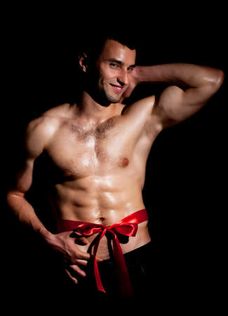 Fashionable muscular man in a fashion pose with red bow photo