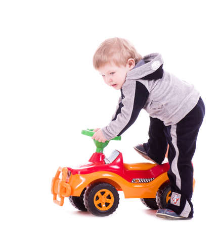Baby boy with a big car on white background photo