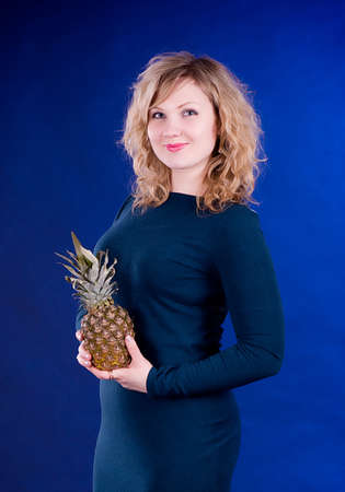 Beautiful young woman with pineapple on dark background photo