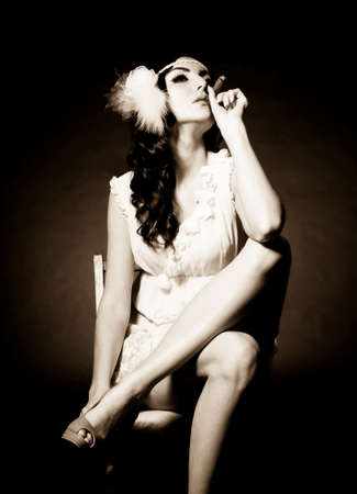 Vintage woman in retro dress with cigar on dark background  Pin-up girl photo