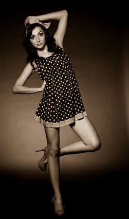 Vintage woman in retro dress on dark background  Pin-up girl photo