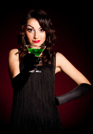 Vintage woman in retro dress with absinthe on dark background  Pin-up girl photo