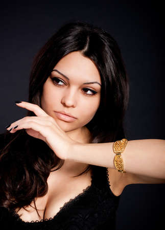 Portrait of beautiful young woman with golden jewelry on black background