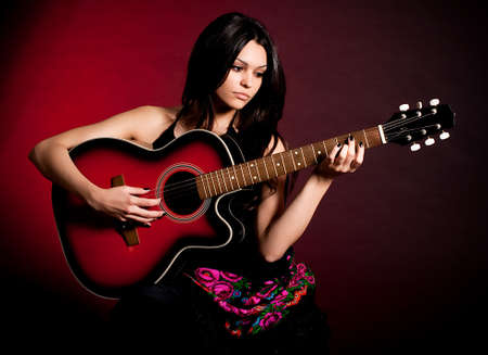 Carmen beautiful woman with guitar on dark background photo