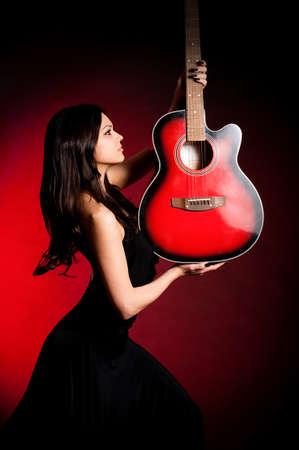 Carmen beautiful woman with guitar on dark background photo