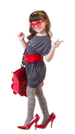 Funny little girl trying on her mother s accessories and shoes on a white background