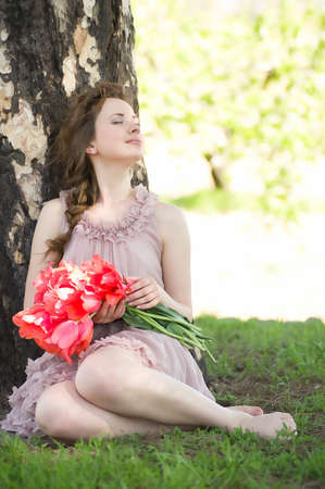 Beautiful woman with red spring tulips in a garden Stock Photo - 13614124