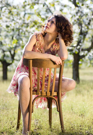 Beautiful woman sits on a chair in a spring garden photo