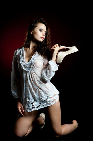Beautiful young woman in wet shirt on dark background photo