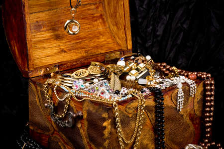Old wooden open chest with golden jewelry photo