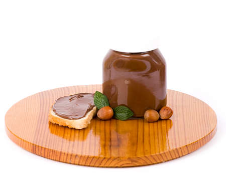 Chocolate spread container with a buttered toast and nuts photo