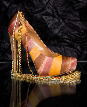 Sexy fashionable shoe with golden jewelry on background Stock Photo - 13663133