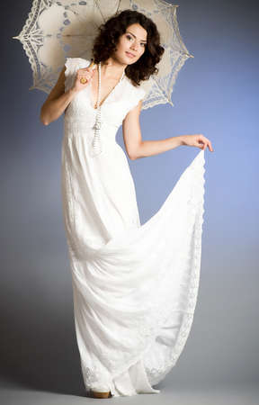 Young woman in retro bridal dress with umbrella on background  photo