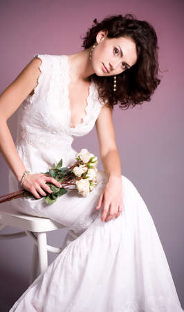 Young woman in retro bridal dress with bouquet from roses  on background  photo
