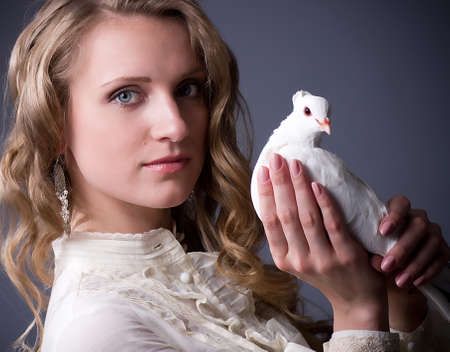 Beautiful woman with white dove on dark background photo