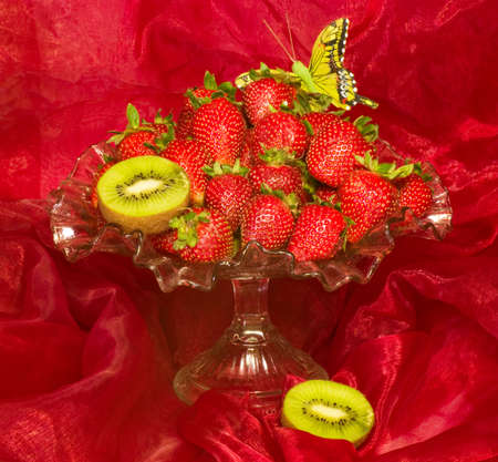 Red fresh strawberry in vase on red background photo