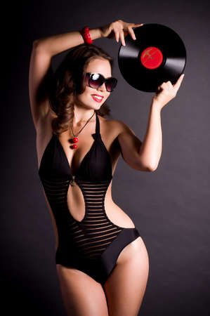 Sexy young woman in retro style with vinyl plate on black background  photo