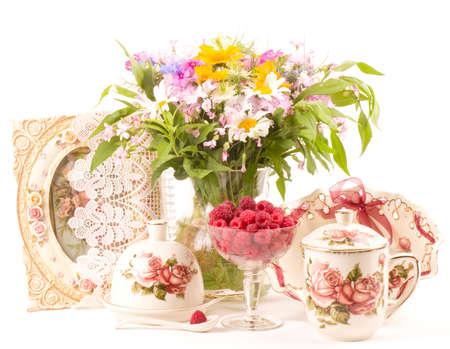 Vintage tea in elegant cups, raspberry and flowers 스톡 콘텐츠