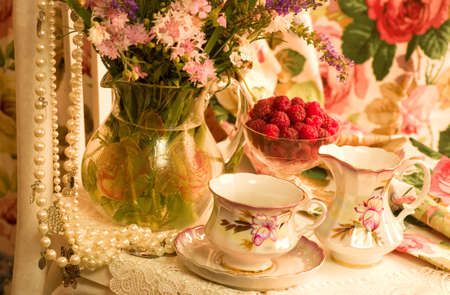 Vintage tea in elegant cups, raspberry and flowers photo