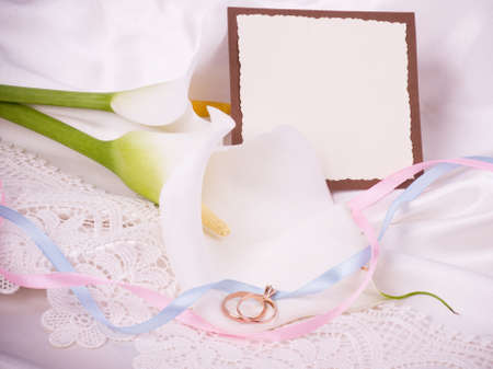 Beautiful white callas with banner add and wedding golden rings photo