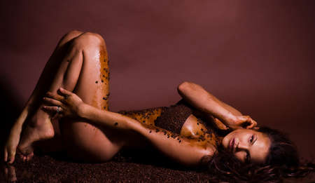 sexy naked girl: Sexy young woman in coffee beans with beautiful brown make-up Stock Photo
