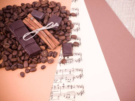Coffee beans, cinnamon and chocolate on a paper background photo