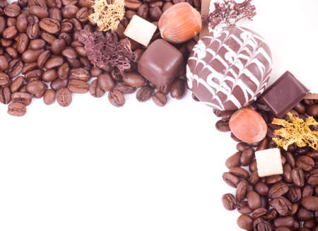 Coffee beans and sweetnesses on white background photo