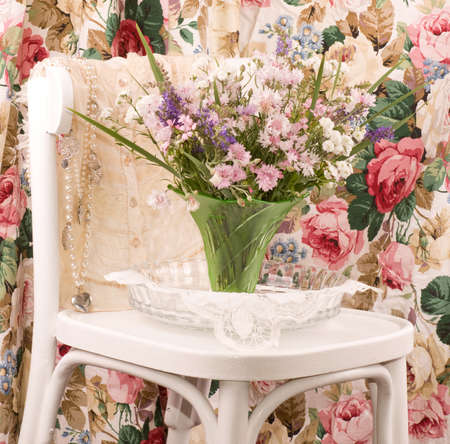 vase with flowers and female cloth on white chair