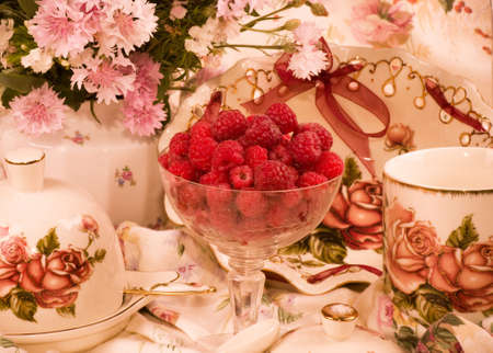 Vintage elegant teacups, raspberry and flowers photo