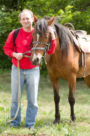 two stroke: Handsome smiling man with horses in the forest