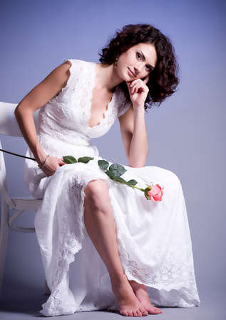 Young woman in bridal dress with rose on background  photo