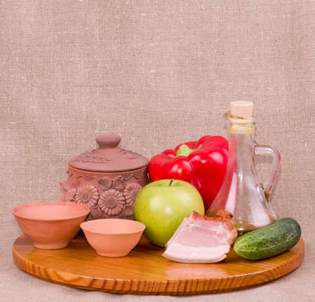 Clay pots, apple, vegetables, oil and meat pork photo