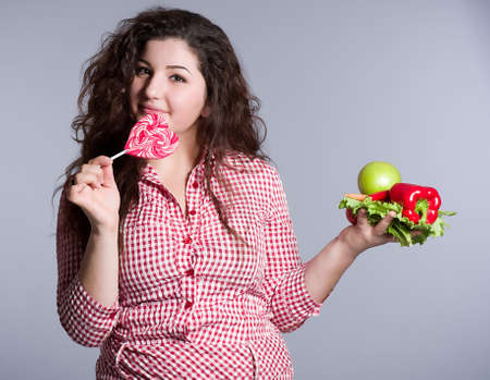 Female vegetarian with vegetables and candy photo