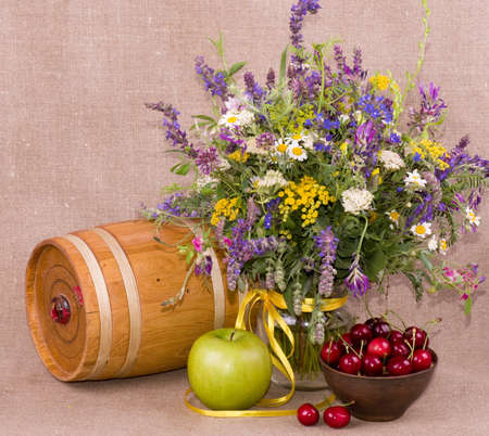 Flowers, barrel, apple and cherry on background photo